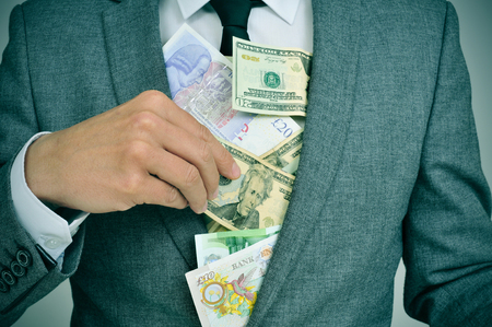 american banker: man in suit putting euro, dollar and pound bills in his jacket, depicting concepts such as greediness, corruption or misappropriation