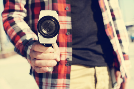 Gros plan d'un jeune homme pointant une caméra Super 8 à l'observateur comme si ce était une arme à feu Banque d'images