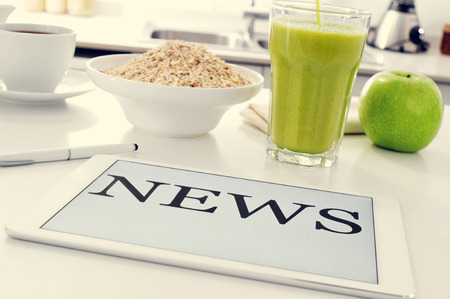 news current events: closeup of the kitchen tablet set for breakfast with a bowl with cereal, an apple and a glass with a smoothie and a tablet computer where to read the news