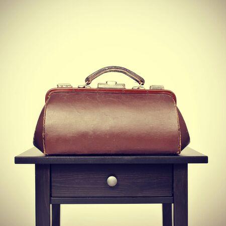 eine alte Arzttasche auf einem Tisch, mit einem Retro-Filter-Effekt