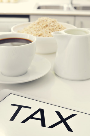outgoings: the word tax written in the screen of a tablet, on a set table for breakfast Stock Photo