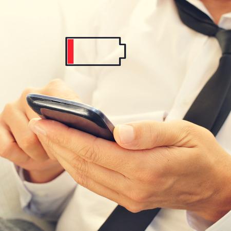 pila: un joven usando un teléfono inteligente y una ilustración de una batería baja Foto de archivo