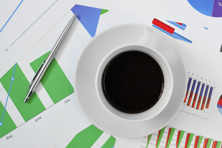 high-angle shot of a cup of coffee on a desk full of charts in the office photo