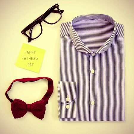 high-angle shot of a table with some mens stuff, such as a plastic-rimmed eyeglasses, a bow tie and a shirt, and a sticky note with the text happy fathers day written in it photo