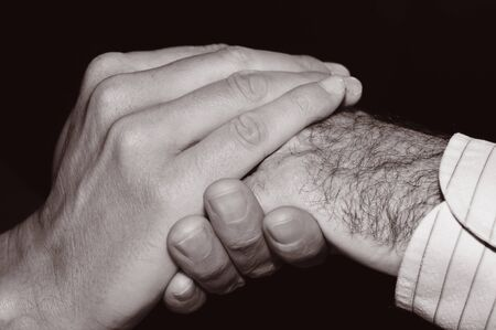 gerontology: closeup of a young man holding the hand of an old man, in black and white