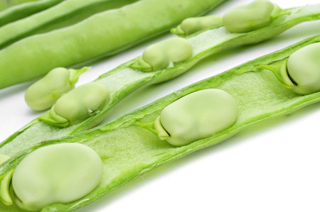 closeup of some broad beans in its pods on a white background photo