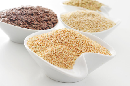 brown flax: some bowls with amaranth, brown flax, quinoa and buckwheat seeds on a white surface