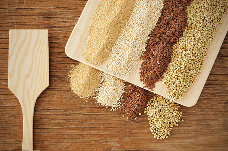 organic flax seed: some piles of amaranth, quinoa, brown flax and buckwheat seeds on a rustic wooden table