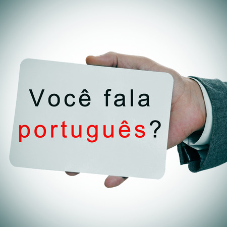man hands showing a signboard with the sentence voce fala portugues? do you speak portuguese written in it photo