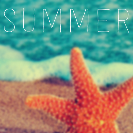 the word summer written on a blurred image of a starfish in the seashore photo