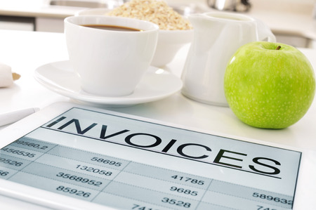 ruination: a tablet computer with a spreadsheet of invoices and a cup of coffee, a bowl with cereals and an apple on the kitchen table Stock Photo