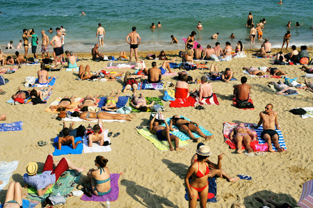Barcelona, Spain - August 19, 2014: Bathers in La Barceloneta Beach in Barcelona, Spain. This popular beach hosts about 500,000 visitors from everywhere during the summer season Éditoriale
