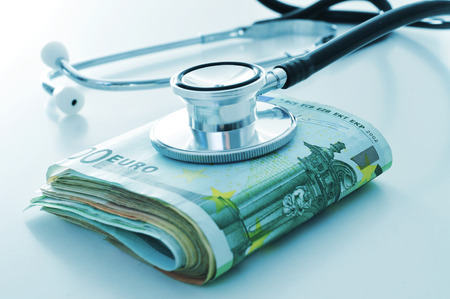 health care costs: a stethoscope on a wad of euro bills, depicting the concept of the health care industry or the health care costs Stock Photo