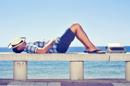 an old typewriter with a blank page and a young man lying down in a street bench near the sea, while is waiting for inspiration Stock Photo