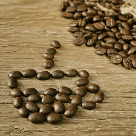 coffeebeans: a pile of roasted coffee beans in the shape of a cup of coffee a wooden table