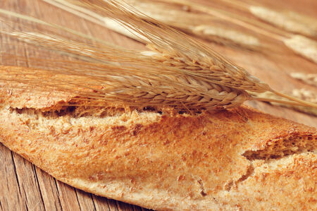 closeup of a whole wheat baguette and some ears of wheat on a rustic wooden table