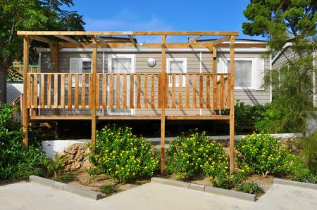 een mooie stacaravan met een houten veranda in een camping