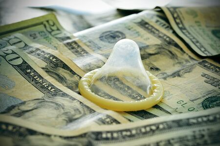 prostitution: a condom on a pile of dollar banknotes