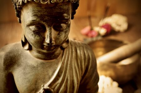 spiritualism: closeup of a buddha with flowers in the background