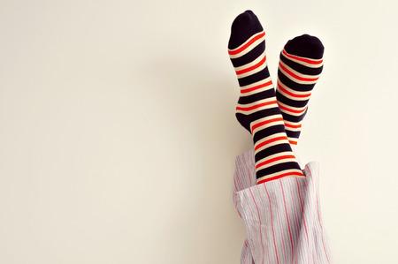 pies masculinos: Primer plano de un hombre joven en pijama con los pies contra la pared Foto de archivo