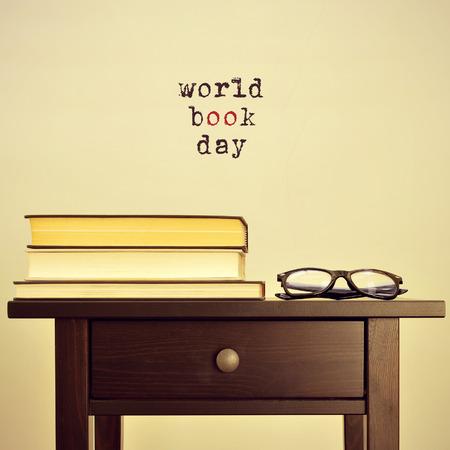 Anteojos negros y algunos libros sobre una mesa y el día frase del libro del mundo sobre un fondo de color beige, con un efecto retro Foto de archivo - 37351627
