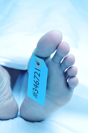 accident dead: closeup of the feet of a dead body covered with a sheet and with a tag with an identification number tied on the big toe