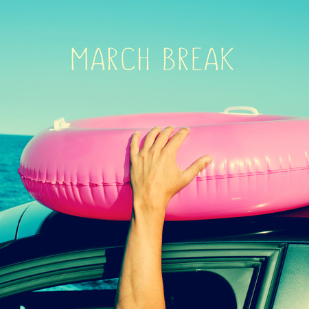 a young man holding a pink swim ring in the roof of a car near the ocean and the text march break written in the blue sky photo