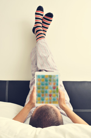 men socks: a young man in pajamas in bed using a tablet with his feet against the wall