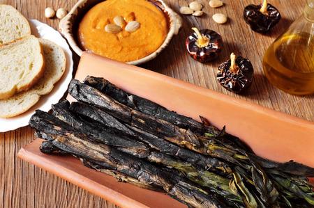 タイルとグリル、ロメスコ ソース、カタルーニャ、スペインの典型的なボウルで提供していますいくつかのバーベキューの calcots、甘い玉ねぎのク