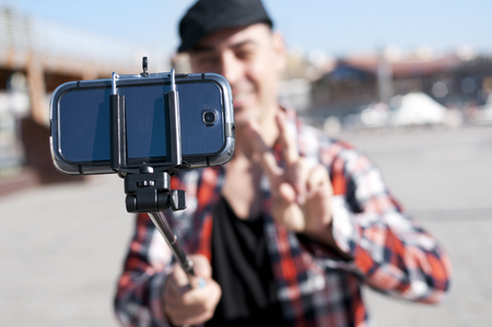salutation: a young man taking a self-portrait with a selfie stick while gives a V sign