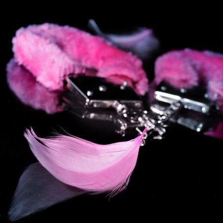 een paar roze sexy fluffy handboeien en een aantal roze veren gebruikt als volwassen speelgoed op een reflecterende zwarte achtergrond
