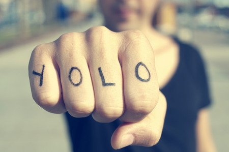 closeup of a young man with the word yolo, for you only live once, tattooed in his hand, with a filter effect Фото со стока