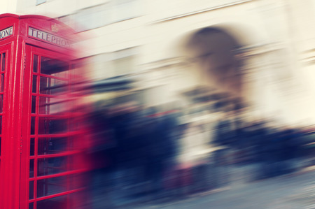 a defocused blur background of people walking in a street in London, United Kingdom, with a typical red telephone booth in the foreground photo