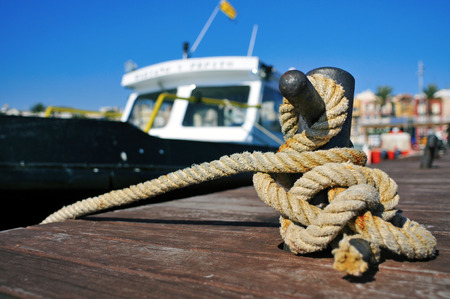 mooring: closeup of a boat tied with a rope on a mooring Stock Photo