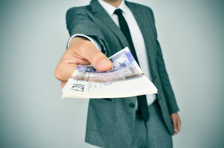un jeune homme en costume de donner une liasse de billets en livres sterling à l'observateur
