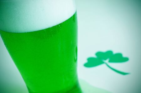 three leaved: a glass with dyed green beer and a three-leaved shamrock, for saint patricks day