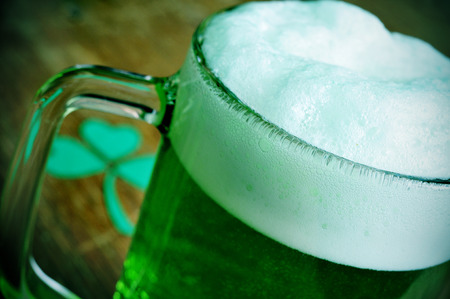 three leaved: a glass mug with dyed green beer and a three-leaved shamrock on a wooden table, for saint patricks day Stock Photo
