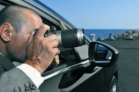 private investigator: a detective or a paparazzi taking photos from inside a car