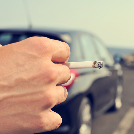 suspected: closeup of a man with a burning cigarette in his hand while is waiting besides a car parked next to a no traffic road