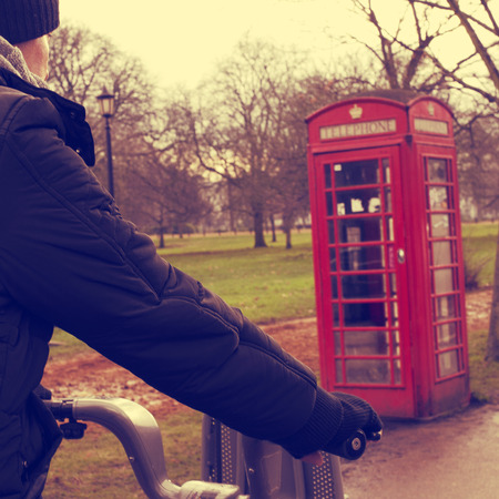 a young man riding a bicycle in Hyde Park in winter in London, United Kingdom, with a typical red telephone booth in the background photo