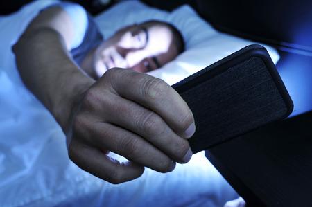 cama: Primer plano de un hombre joven en la cama mirando el teléfono inteligente en la noche