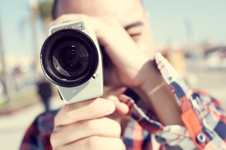 acion: un joven con una camisa a cuadros de filmación con una cámara Super 8 al aire libre Foto de archivo