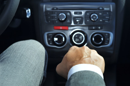 travelling salesman: closeup of a young man in suit driving a car with manual transmission
