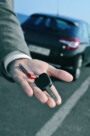 car retailer: man in suit offering a car key to the observer, with a car in the background Stock Photo