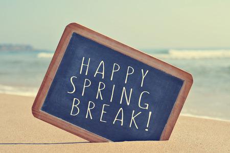 le texte vacances de printemps heureux écrit dans un tableau noir sur le sable d'une plage, avec un effet de filtre Banque d'images