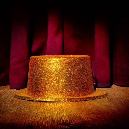 dramatic characters: a golden top hat on a stage with the theater curtain in the background