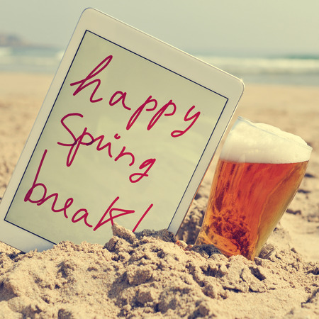 a glass with bear and a tablet with the text happy spring break written in it on the sand of a beach, with a filter effect