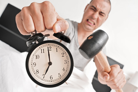 stressing: a young man  in bed about to hammer his alarm clock at seven in the morning