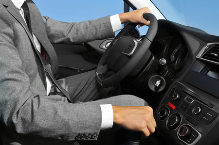 travelling salesman: a young man wearing a suit driving a car with manual transmission