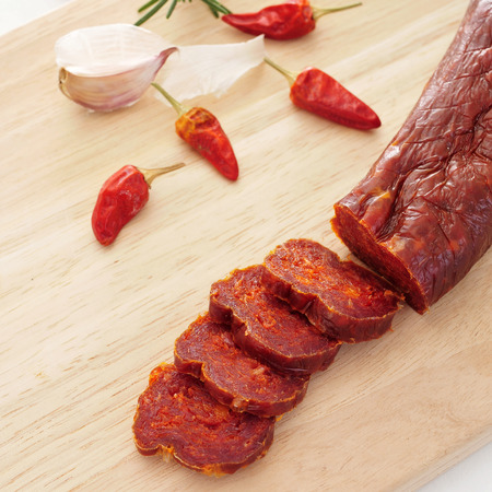 embutido: a piece of spanish chorizo and some slices on a chopping board